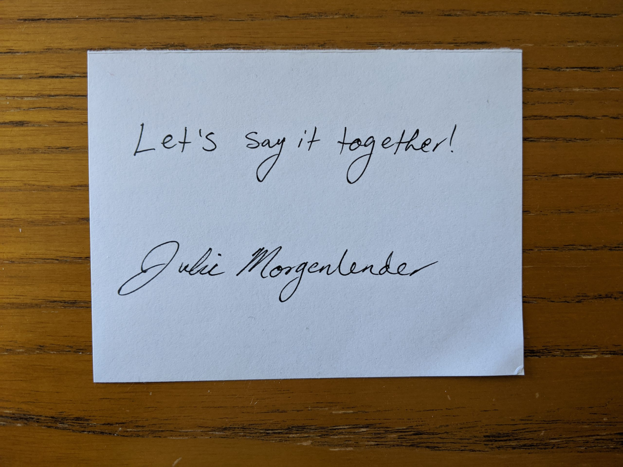 "White cardwith text ""Let's say it together!"" and signature beneath text."
