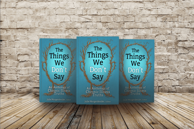 The copies of book The Things We Don't say lined up in front of a white brick wall